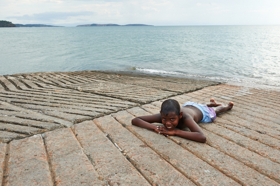 Young Indigenous boy from Palm Island laying on ramp near ocean smiling after being assisted by our Indigenous Support Services.