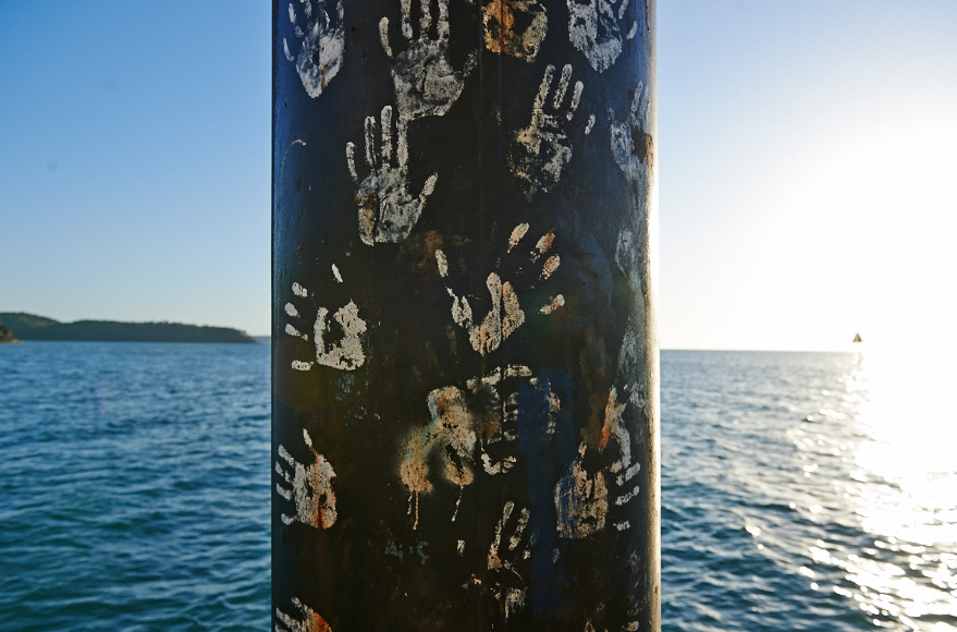Our Community Development Program runs in Palm Island where this photo was taken of a pier pillar that has hand prints of community members on it demonstrating the link to past and present community members.