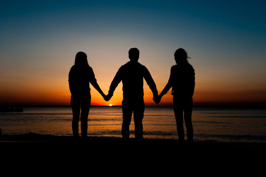 Silhouette of three friends in the morning at the beach, holding hands and waiting for the sunrise. Support, together, winning, helping, freedom concept.